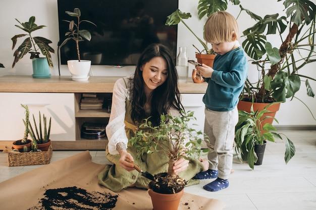 Madre con hijo pequeño cultivando plantas en casa