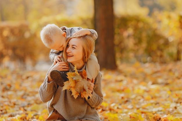 Madre con hijo pequeño jugando en un campo de otoño