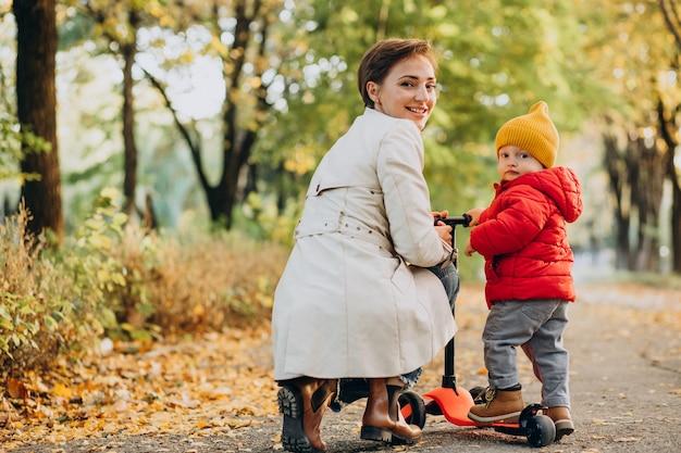 Madre con hijo pequeño en scooter en parque otoñal