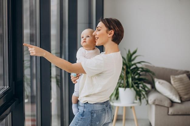 Madre con hijo de pie en casa junto a la ventana