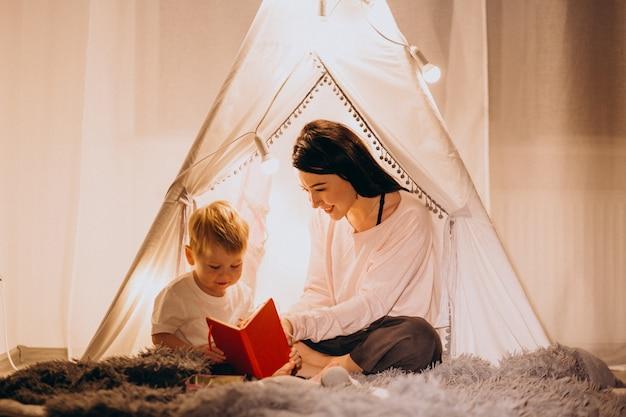 Madre con hijo sentado en una acogedora carpa con luces en casa en navidad