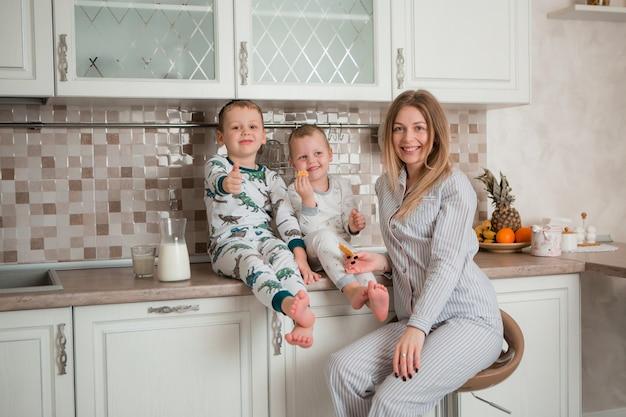 Madre con hijos desayunando en la cocina