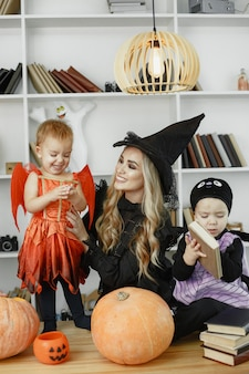 Madre con hijos en disfraces y maquillaje.
