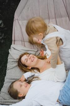 Madre con hijos divirtiéndose en una hamaca. mamá e hijos en una hamaca. t