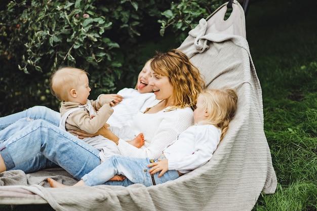 Madre con hijos divirtiéndose en una hamaca. mamá e hijos en una hamaca.