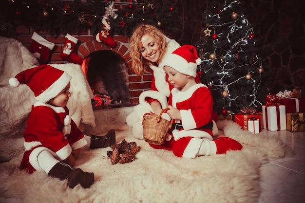 Madre con hijos están sentados cerca de la chimenea y juegan con conos - adornos navideños