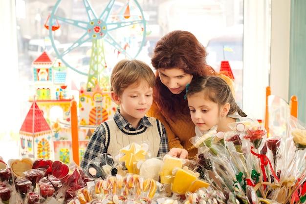 Madre con hijos felices en la tienda de golosinas