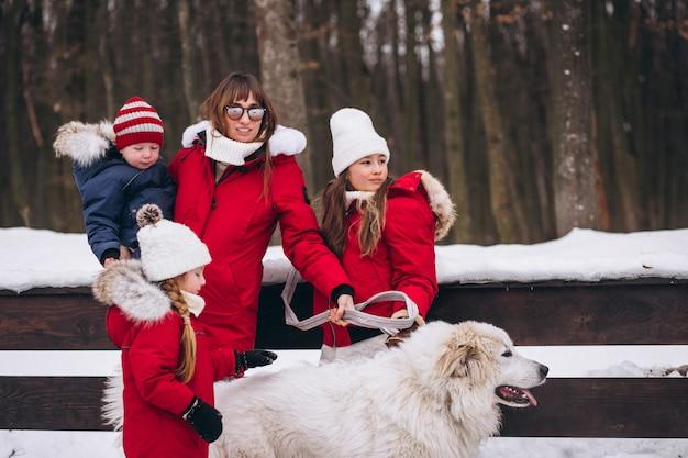 Madre con hijos y perro jugando afuera en invierno.