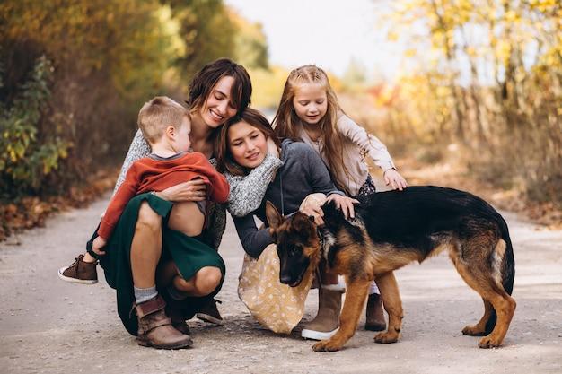 Madre con hijos y perro en un parque de otoño