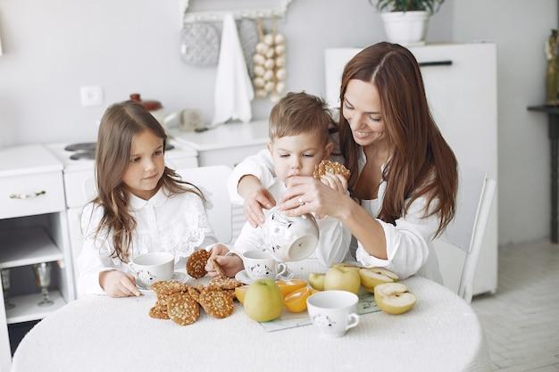 Madre con hijos sentados en la cocina y comer