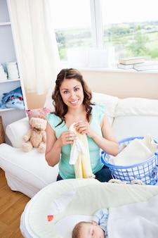 Madre joven alegre que hace la ropa mientras que su bebé está durmiendo en la sala de estar