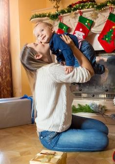 Madre joven alegre sosteniendo y jugando con su hijo en el piso en el árbol de navidad