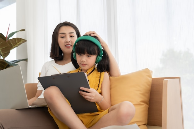 Madre joven asiática con niño de enseñanza portátil en casa
