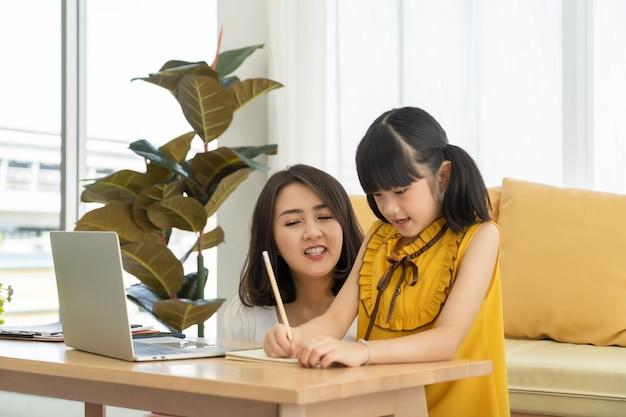 Madre joven asiática con ordenador portátil que enseña al niño a aprender o estudiar en línea en casa