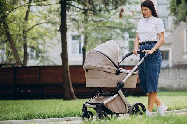 Madre joven caminando con cochecito de bebé en el parque