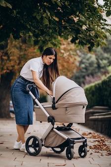Madre joven caminando con stoller en estacionamiento