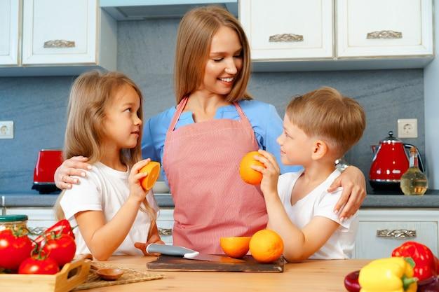 Madre joven cocinando con sus hijos en la cocina