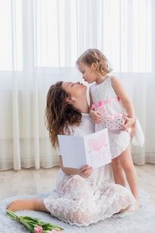 Madre joven e hija que se besan en casa con sostener la tarjeta de felicitación