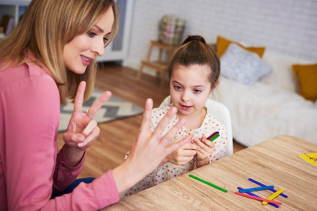 Madre joven enseñando al niño a contar en casa