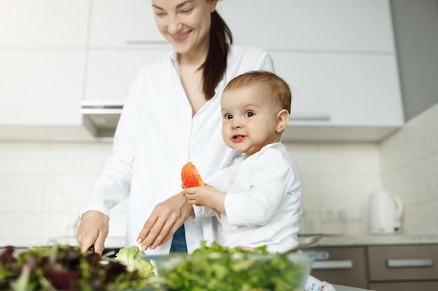 Madre joven feliz que cocina el desayuno en la cocina ligera con su pequeño hijo lindo. niño comiendo melocotón con expresión divertida mientras mamá trabaja.