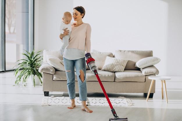 Madre joven con hijo pequeño limpiando en casa