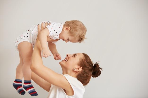 Madre joven jugando con su pequeño bebé en la cama