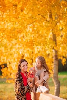 Madre joven con niña linda en el parque de otoño en un día soleado. familia disfruta de un clima cálido en el día de septiembre.