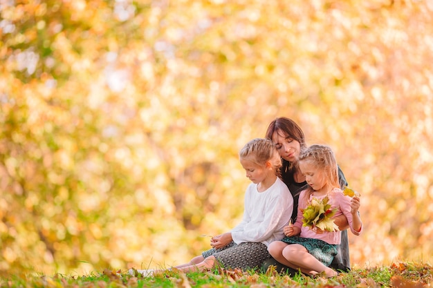 Madre joven con niñas lindas en el parque de otoño en un día soleado. familia disfruta de un clima cálido en el día de septiembre.