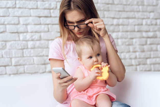 Madre joven con el pequeño bebé que usa smartphone