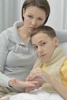 Madre joven preocupada e hijo enfermo en la cama