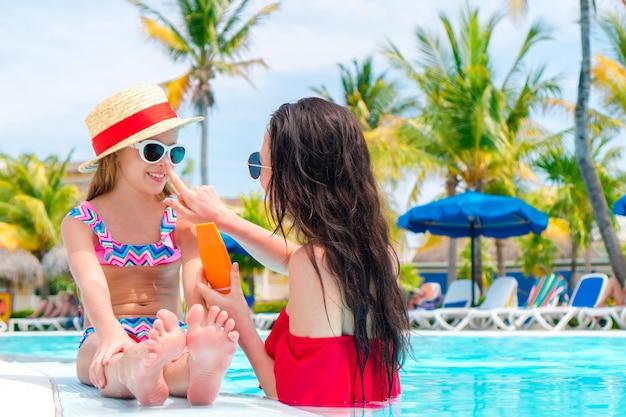 Madre joven que aplica la crema del sol a la nariz del niño en piscina