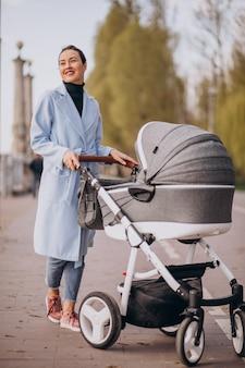 Madre joven que camina con el carro de bebé en parque
