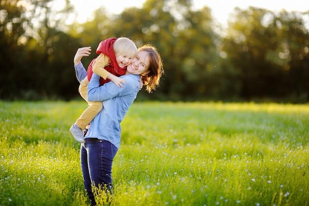 Madre joven que celebra a su pequeño hijo durante paseo en el campo de flores