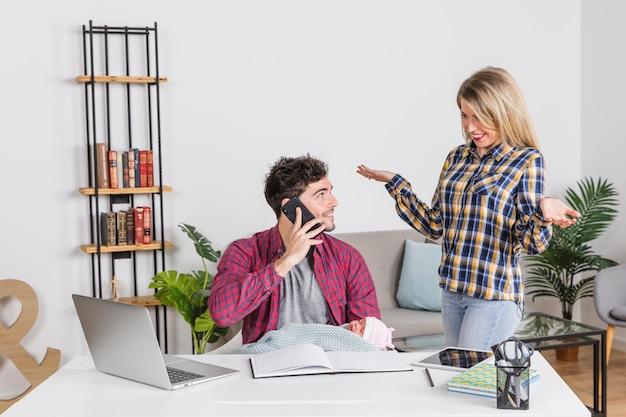 Madre joven que mira al padre con el bebé que habla en el teléfono