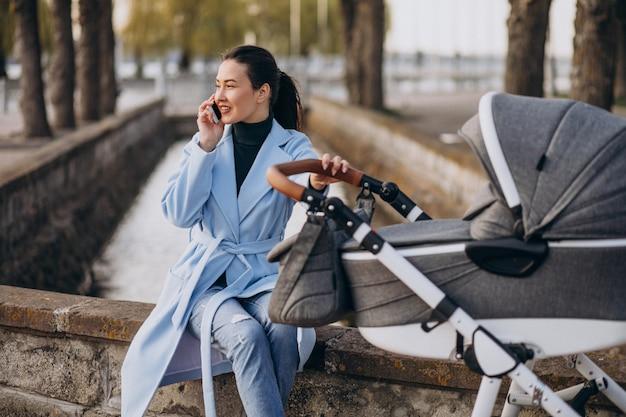 Madre joven que se sienta con el carro de bebé en parque