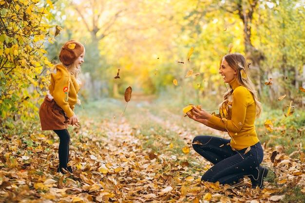 Madre joven con su pequeña hija en un parque del otoño