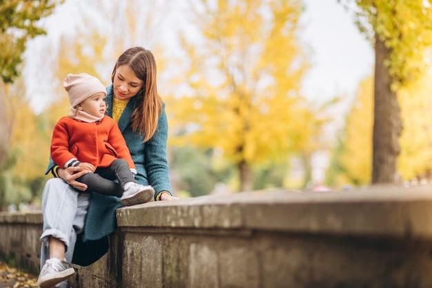 Madre joven con su pequeña hija en un parque de otoño