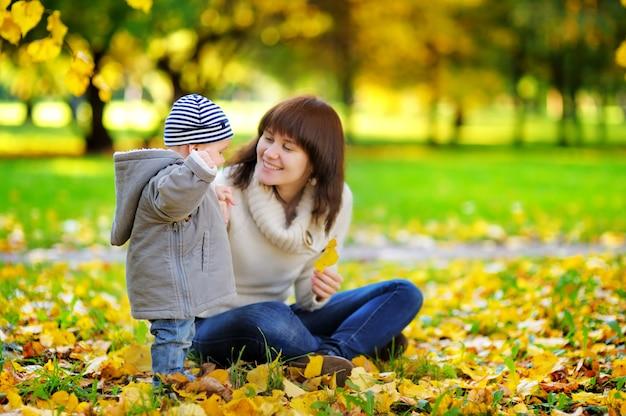 Madre joven con su pequeño bebé que se divierte en el parque del otoño