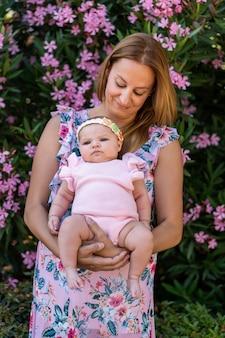 Madre joven con un vestido con flores sosteniendo a su pequeña niña