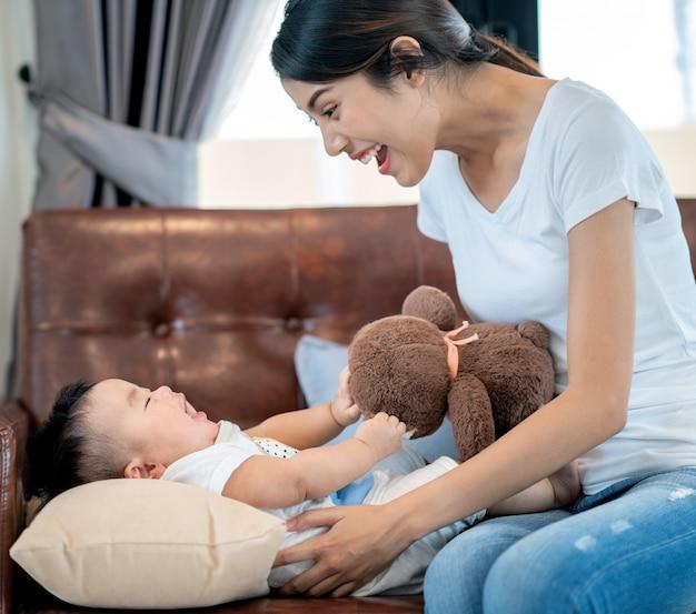 Madre juega con su bebé por osito de peluche