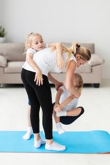 Madre jugando con hijas en casa mientras hace ejercicio