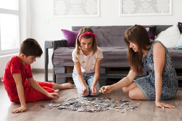 Madre jugando rompecabezas con sus hijos en casa