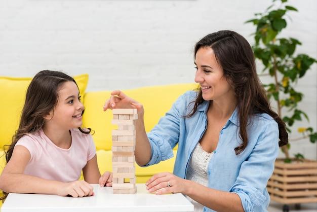 Madre jugando con su pequeña hija un juego de mesa