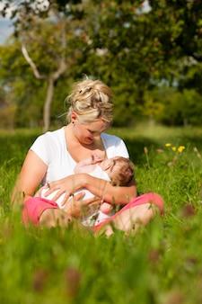 Madre lactante bebé en pradera