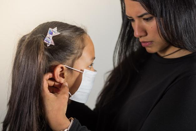 Madre latina pone la máscara a su hija