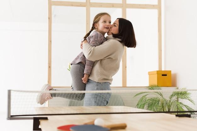 Madre levantando linda hija en el interior
