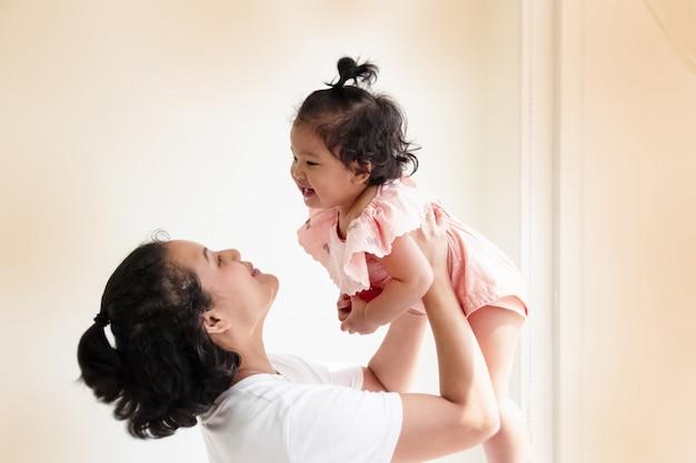 Madre levantando a su hija en el aire, con una sonrisa y una cara feliz.