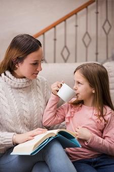 Madre leyendo junto con hijas