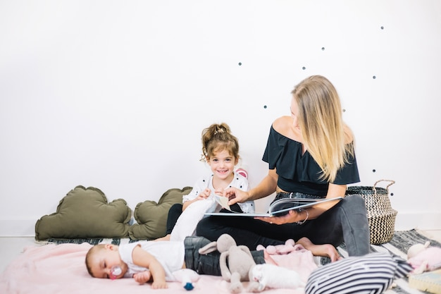 Madre leyendo el libro a la niña y al bebé