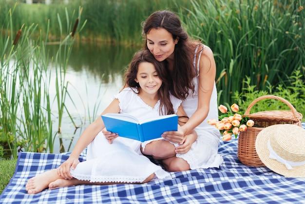 Madre leyendo libro a su hija junto al lago.